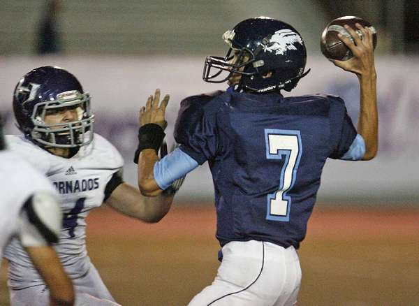 ARCHIVE PHOTO: Crescenta Valley High quarterback Brian Gadsby, right, will look to keep the Falcons' offense clicking in a rivalry game with La Cañada.