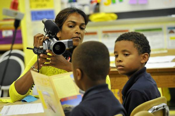 "Ramona Persaud, producer of ""Grey Matters,"" films Josiah Johns (left), 9, as he reads. At right, Avon Johnson, 9, listens. Persaud is working on a documentary about the Brain-Targeted Teaching Model and Roland Park Elementary/Middle School is one of the schools featured."