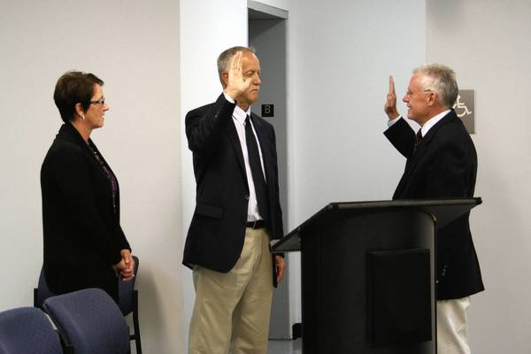 "Mayor Jim Holland, right, swears in Neil Nunamaker, center, for a post on the village Plan Commission during the Sept. 16 Frankfort Village Board meeting. Standing beside Nunamaker is his wife, Betsy. Holland said Nunamaker studied criminology but went on to become a schoolteacher. ""I know you'll bring a real level-headed, sincere approach,"" Trustee Mike Stevens said."