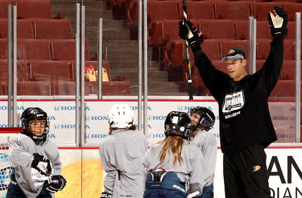 Ryan Getzlaf works with participants in the Learn to Play hockey program.