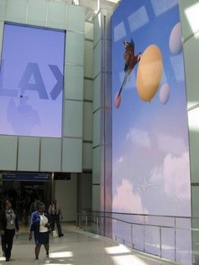 Passengers who have passed through airport security will encounter the Bon Voyage Wall before heading into the Great Hall and departure gates. The wall shows images of people jumping in slow motion.