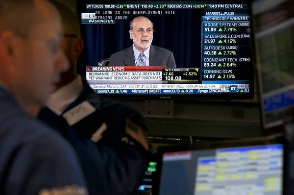 Federal Reserve Chairman Ben Bernankes televised news conference is shown at the New York Stock Exchange. He defended the Feds surprise move.