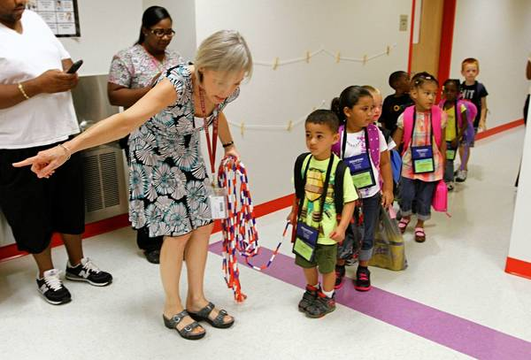 First day of School, Teachers Asst. Cathryn Walls points to the class room for the new Pre-K students at Phenix school this morning.