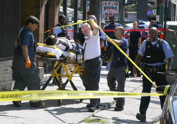 Chicago firefighters and paramedics transport a shooting victim near a liquor store at 79th Street and Cottage Grove Avenue on Sept. 5. An abstract of a new study by Northwestern University says those near a liquor store or bar on the South or West sides are about 500 times more likely to be shot than other people in the neighborhood.