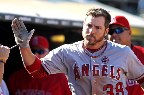 Angels left fielder J.B. Shuck high-fives teammates after scoring against the A's in the 11th inning on Wednesday.