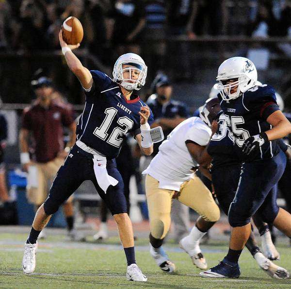 Liberty's Douglas Erney (left) makes a pass during their game with Whitehall High School on Friday September 6, 2013.
