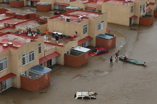 Residents wait for help in Acapulco. Mexican authorities scrambled Tuesday to launch an airlift to evacuate tens of thousands of tourists stranded amid flooding after a pair of deadly storms. The official death toll rose to 80 on Wednesday after Hurricane Ingrid and Tropical Storm Manuel pounded large swaths of the country.