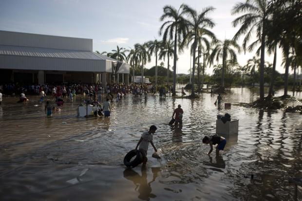 People wade through waist-high water looking for valuables in the parking lot of a store in Punta Diamante, south of Acapulco.