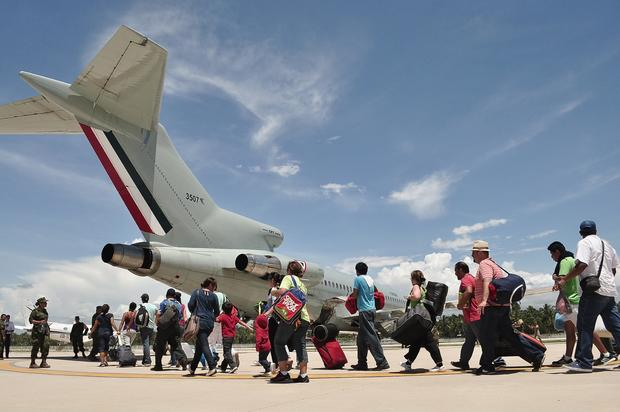 Stranded tourists board a Mexican air force plane at a military base in Acapulco.