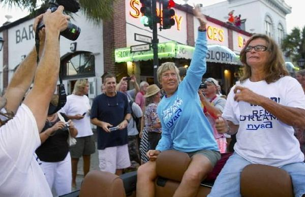 Endurance swimmer Diana Nyad (L) and her chief handler Bonnie Stoll (R) ride in vehicle during a parade past Sloppy Joe's Bar in Key West, Florida September 3, 2013, a day after Nyad completed a Cuba-to-Key West swim that took 52 hours and 54 minutes.
