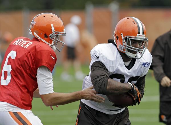 Cleveland quarterback Brian Hoyer hands the ball off to running back Trent Richardson on Wednesday, the same day Richardson was traded to Indianapolis and Hoyer was named the Browns' starting QB for this week.