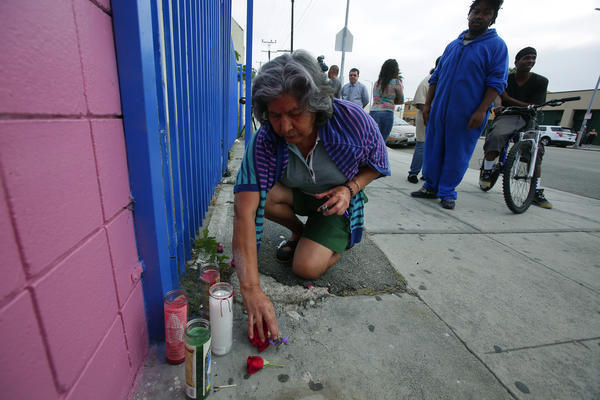 Area resident Elsa Cabrera, 67, lights a candle at a makeshift memorial in front of the store where clerk Martha Sanchez, a 39-year-old mother of five, was fatally shot Tuesday night.