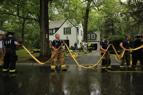 Firefighters pack up after extinguishing a two-alarm fire in the 300 block of Ravine Park Drive in Lake Forest after lightning struck a tree and jumped to the attic, according to Lake Forest Dept. Fire Chief Kevin Issel.