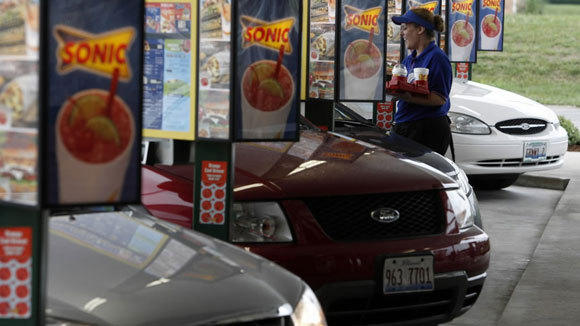 Heather Morris delivers food to customers at Sonic Drive-in Jacksonville, Ill., in a 2006 file photo.