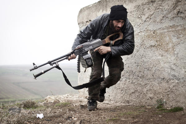 A Free Syrian Army fighter takes cover during clashes with government forces in Azaz in December.