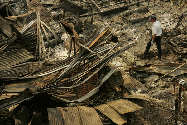 An employee with Malibu Glass & Mirror walks through the rubble of the business after the October 2007 Malibu Canyon fire.