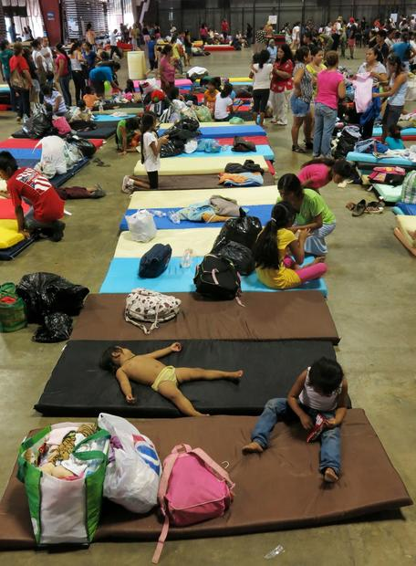 Residents from La Pintada rest inside the Acapulco Convention Center after Tropical Storm Manuel caused a landslide that buried houses in their village.