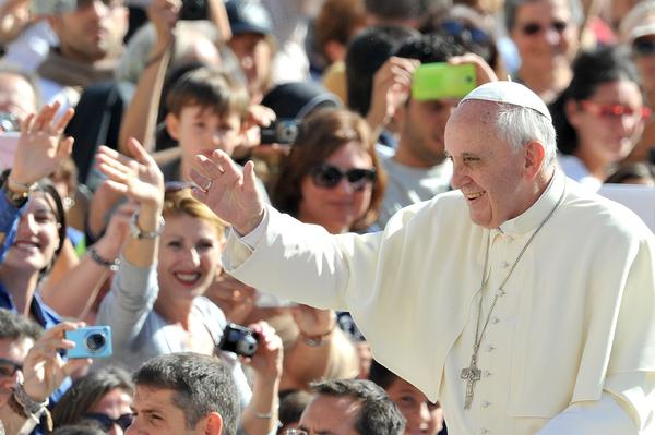 Pope Francis waves to the crowd as he arrives for a general audience in St. Peter's Square at the Vatican.