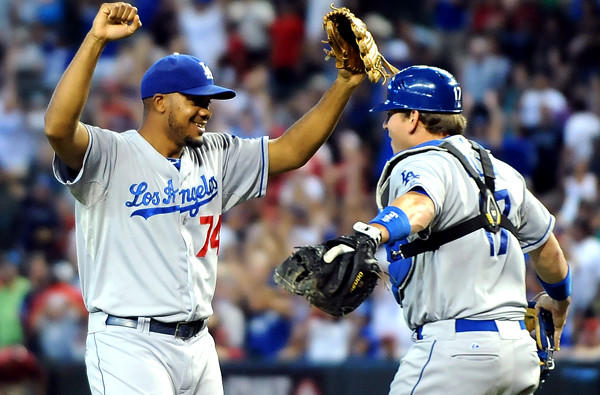 Dodgers closer Kenley Jensen and catcher A.J. Ellis celebrate after the final out in a 7-6 victory over the Diamondbacks at Chase Field in Phoenix on Thursday afternoon.