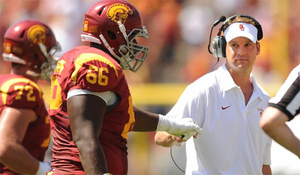 USC Coach Lane Kiffin fist bumps Marcus Martin after a Trojan touchdown against Boston College on Saturday.