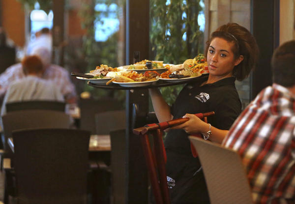 Chenise Berens carries a tray of food to a table as she works her shift Wednesday night at Mavericks Steak and Cocktails. With three new restaurants opening this fall, the competition for restaurant workers is intense. Cooks, wait staff and bartenders are in demand. American News Photo by John Davis