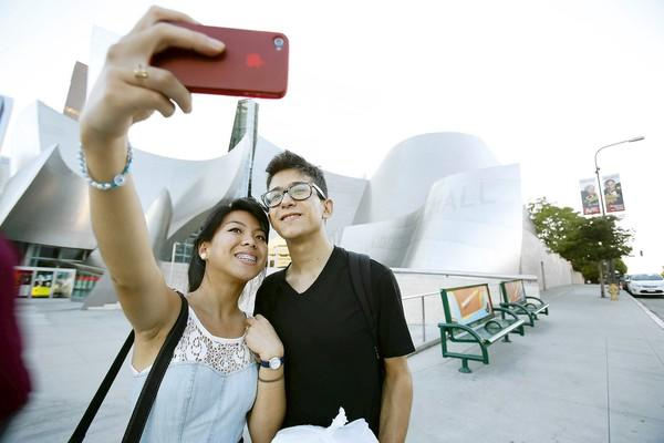 Madison Villanueva of Van Nuys uses her phone to take a photo of herself and Magdalenno Rosales of Los Angeles at Disney Hall.