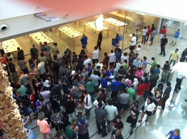 A crowd of people wait to enter the Apple store at the Mall at Millenia to buy a new iPhone5S or iPhone5C.