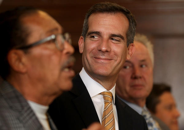 Los Angeles Mayor Eric Garcetti breaks into a smile during a news conference at City Hall last month. He'll be taking questions from the public at a curbside desk Friday in Boyle Heights.