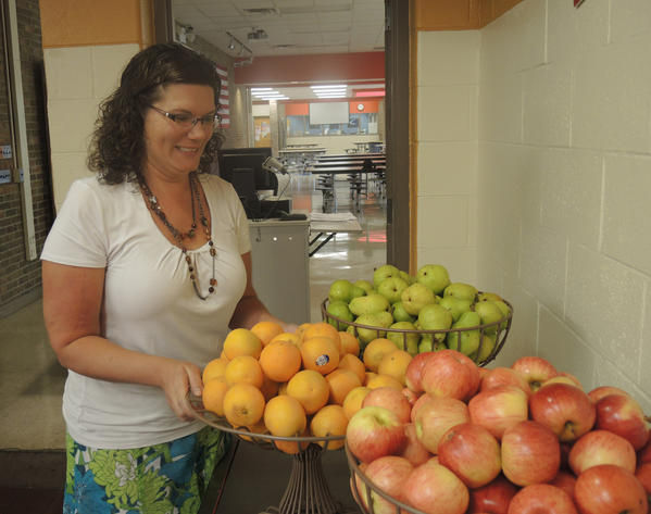 Beth Kavanaugh, Chartwells Food Service Director at Petoskey Public Schools, sets out a tray of fresh oranges in preparation for the high school lunch.