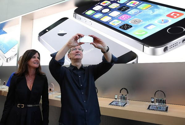 Katie Cotton, Apple vice president of corporate communications (L) looks on as Apple CEO Tim Cook (R) uses an iPhone to take a picture of customers waiting in front of an Apple store to purchase the new iPhones on September 20, 2013 in Palo Alto, Calif.