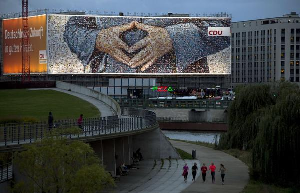 People run by a giant election billboard in Berlin featuring German Chancellor Angela Merkel's famous diamond-shaped hands pose. German voters go to polls Sunday for the general election.