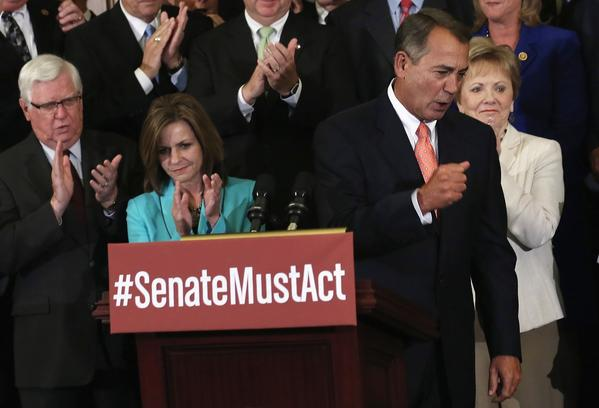 House Speaker John A. Boehner (R-Ohio), at the podium, leads a rally of House Republicans after a vote Friday to pass a spending bill that bars funding for the 2010 healthcare law but keeps the government running until Dec. 15.