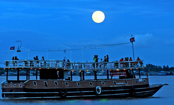 The moon rises as a tourist boat sails along the Mekong River in Phnom Penh, Cambodia.