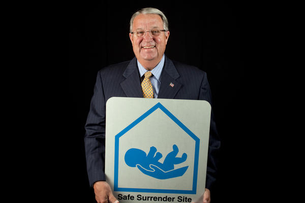 Los Angeles County Supervisor Don Knabe holds a Safe Surrender sign. Knabe initiated the program in 2001.
