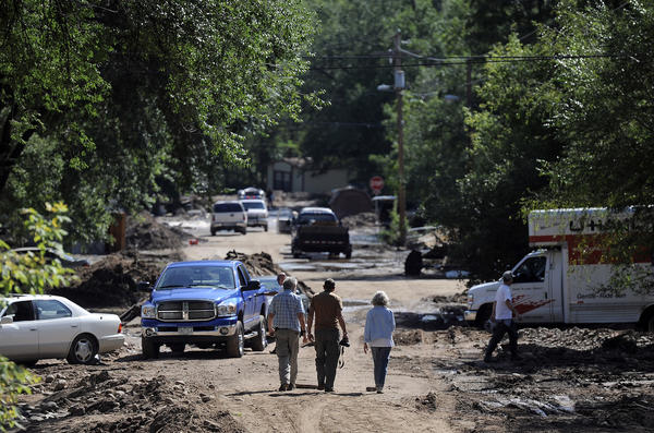 People walk through a severely flooded neighborhood in Lyons, Colo. Residents displaced by last week's flooding in the Colorado canyon town were allowed past National Guard roadblocks Thursday.