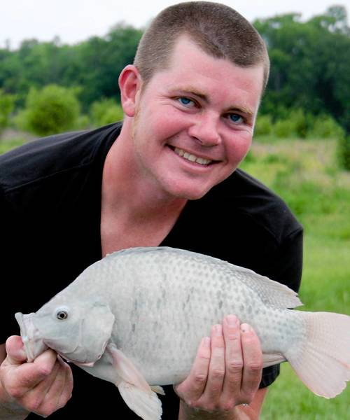 Clermont aquaponics farmer Ryan Chatterson with a tilapia grown at his Chatterson Farms in Clermont.