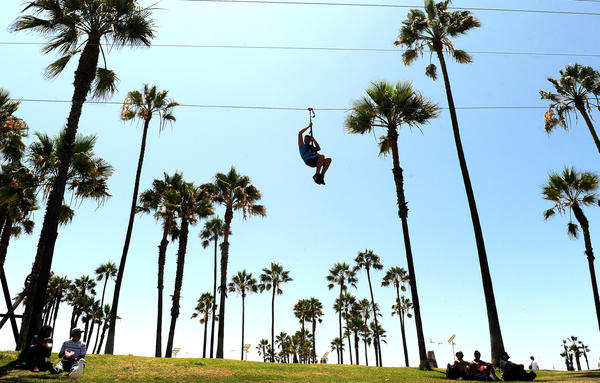 A man rides down a zip line in Venice on a warm Friday afternoon.