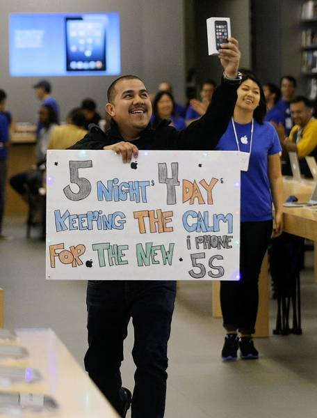 Fransisco Naranjo, 27, celebrates after becoming the first to purchase the new iPhone 5s at the Apple store in Pasadena. He was first in line at the store, waiting since 9 p.m. Sunday.