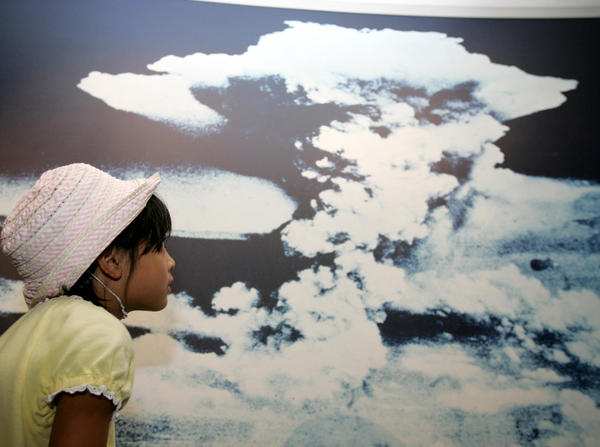 A Japanese girl looks at a photograph of the first atomic bomb blast mushroom cloud at Hiroshima Peace Museum in Hiroshima, Japan.