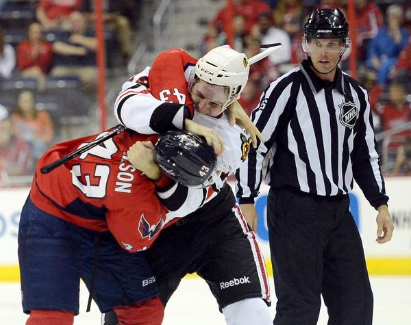 The Capitals' Tom Wilson and Kyle Beach fight as a linesman watches in the second period.