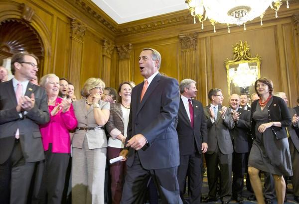 Republican House members cheer Speaker John A. Boehner (R-Ohio) after a vote to approve a spending measure that would prevent funding of President Obama's healthcare law. The Senate is likely to reject it, setting the stage for a possible government shutdown.