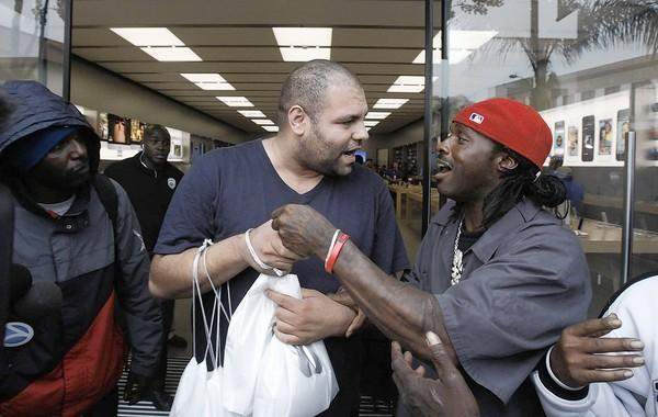 A man, at right, confronts a businessman who had hired him to hold a place in line outside the Apple store in Pasadena. At least two people were arrested after fistfights erupted.
