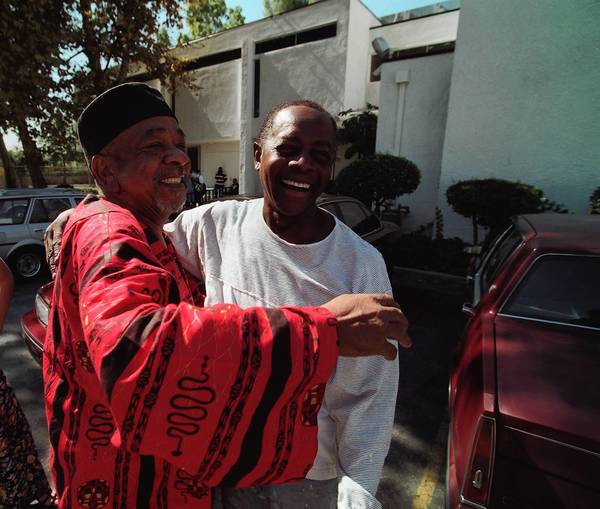 Cecil Fergerson, left, hugs artist Elliott Pinkney outside the Watts Mafundi Institute in 1997, when Pinkney repainted a mural at the site that he'd originally painted years before.