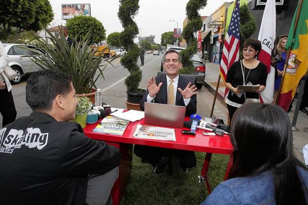 Los Angeles Mayor Eric Garcetti meets with Armando Gonzalez, left, and Leslie Baez during a curbside meeting with constituents on East 1st Street in Boyle Heights. Gonzalez, who runs a skateboard shop, wanted the city's assistance in securing space for a skating academy.