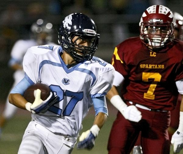 Crescenta Valley High defensive back Byung Kim is chased by La Canada High's Anthony Connell as he runs back an interception during the team's rivalry game in La Caada on Friday. (Raul Roa/Staff Photographer)