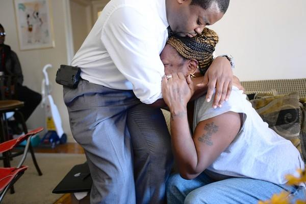 Priscilla Daniels, whose husband, Arthur Daniels, was killed in the mass shooting at the Washington Navy Yard, is comforted by Lynnell Humphrey, a local official who came to assist the family with arrangements.