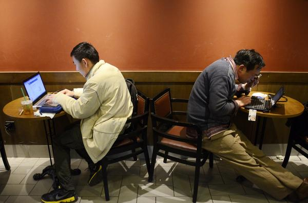 Men use their laptops at a cafe in Beijing. A 16-year-old schoolboy was arrested last week under a controversial new Chinese crime of spreading rumors over the Internet.
