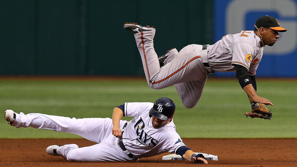 Alexi Casilla turns a double play as David DeJesus #7 of the Tampa Bay Rays slides into second.