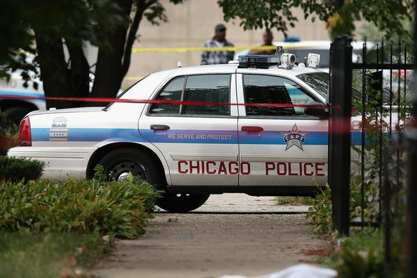 The body of a 14-year-old who was fatally shot in Chicago lies covered by a sheet as police investigate a rash of shootings across the city.