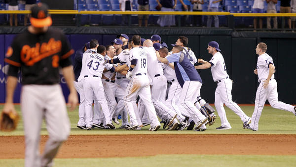 Tampa Bay Rays left fielder David DeJesus (7) is congratulated by teammates after he hit the game winning RBI during the eighteenth inning Saturday morning against the Orioles.